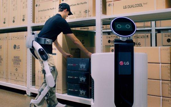 'LG 클로이 수트봇'을 입은 작업자가 물류센터에서 상품을 쇼핑카트 로봇에 담고 있다. /사진제공=LG전자