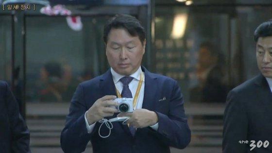 대동강 수산물 식당에서 수족관의 철갑상어를 찍고 있는 최태원 SK회장/사진=평양사진공동취재단3
