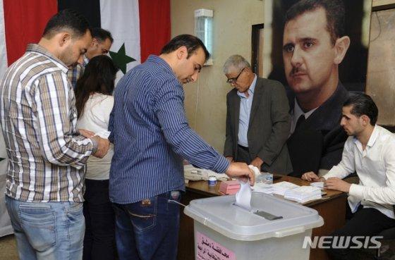 시리아 관영 사나 통신 제공으로, 지난 9월16일 수도 다마스쿠스에서 시의회 선거 투표가 실시되고 있다. 아사드 대통령 사진이 보인다. /사진=뉴시스