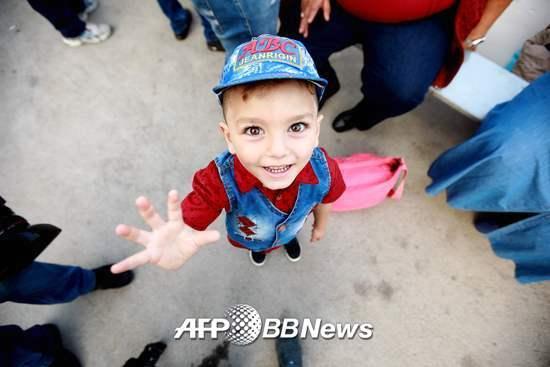 시리아인 아이가 지난 9월17일 카메라를 향해 웃고 있다. 아이는 몇년 간 레바논에 위치한 시리아 난민 캠프에서 지내왔다가 이날 가족과 함께 본국으로 돌아갔다. 시리아 내전이 거의 종식되는 단계여서다. /AFPBBNews=뉴스1