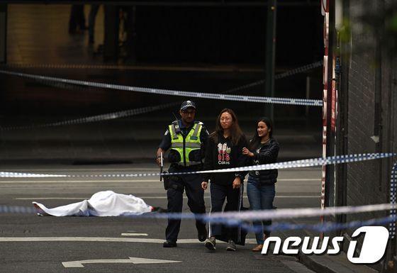 호주 경찰이 9일(현지시간) 멜버른에서 발생한 흉기 난동 사건 현장에서 사람들을 대피시키고 있다. 그 뒤로는 피해자로 보이는 사람이 흰 천을 덮고 있다. © AFP=뉴스1