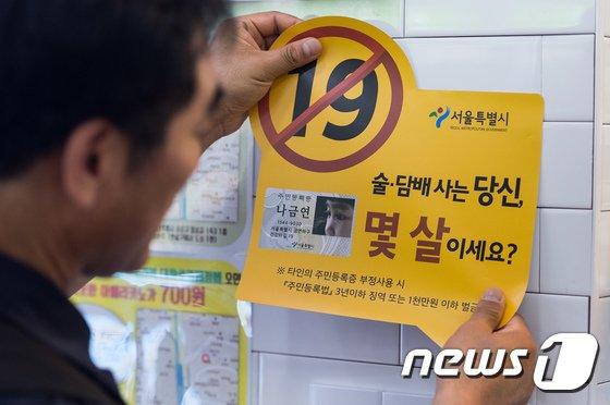 한 편의점에 청소년 대상 술·담배 판매금지 경고문구 스티커를 부착하고 있다. /뉴스1 © News1