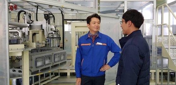 윤진국(45) 이티에스 대표가 19일 충남 아산시에 위치한 본사 공장에서 직원으로부터 생산공정에 관한 이야기를 나누고 있다.