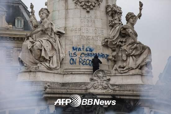 """한 프랑스 시위자가 지난 5월 22일 프랑스 레퓌블뤼크 광장의 석상에 """"그들은(정부는) 68혁명을 기념한다. 우리는 (혁명을) 다시 시작한다""""고 적고 있다. /AFPBBNews=뉴스1"""