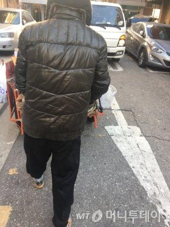 손수레를 끌고 가는 최진철씨(55) 오른편 도로로 흰색 트럭이 지나가려 하고 있다. 좁다란 도로라 피할 공간이 별로 없었다. 그래서 늘상 안전 위험에 노출돼 있다. 최씨도 오토바이 사고로, 허리뼈가 부러졌다고 했다./사진=남형도 기자