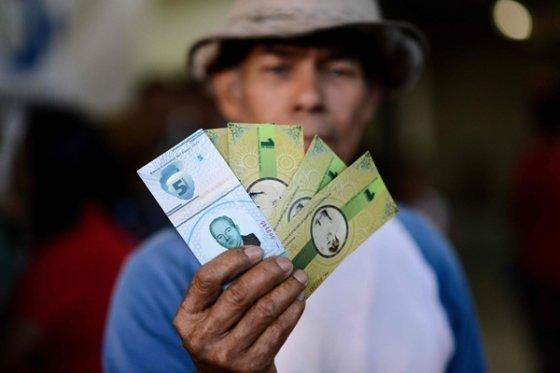 2017년 12월 15일 베네수엘라 수도 카라카스 인근 23 드 에네로 지역의 한 주민이 자체 통화 '파날'(panal)을 들고 있다. 이 지역은 초인플레이션 상황을 타개하기 위해 설탕, 쌀 등과 교환할 수 있는 자체 통화를 발행했다. /AFPBBNews=뉴스1