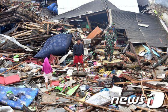 인도네시아 순다 해협 인근을 쓰나미가 강타한 사흘 뒤, 무너진 건물 잔해 위에 서있는 인니 사람들. © AFP=뉴스1