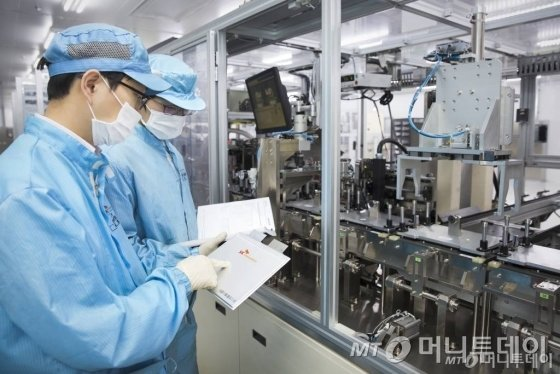 SK이노베이션 서산공장 전기차 배터리 생산라인에서 직원들이 생산된 배터리 셀을 검사하고 있다.