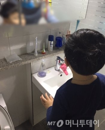 """주환이가 화장실서 양치질을 할 준비를 하고 있다. 주환이 아빠가 어떻게 하는지 알려줬다. 붕 뜬 뒷머리를 깜빡하자, 주환이가 """"뒷머리도 만져주세요"""" 했다(기특)./사진=남형도 기자"""