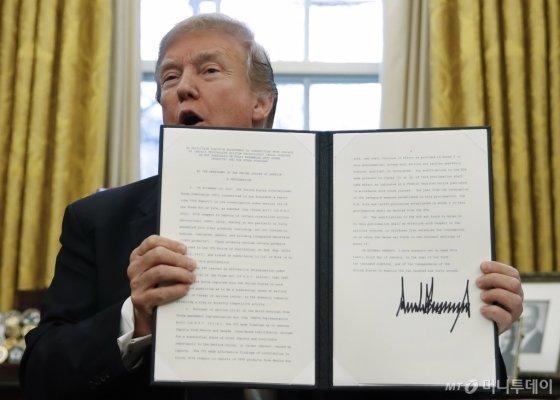 도널드 트럼프 미국 대통령이 2018년 1월23일 백악관에서 수입 세탁기와 태양광 제품에 대한 세이프가드(긴급수입제한) 조치에 서명한 후 문서를 들어보이고 있다/AP 뉴시스