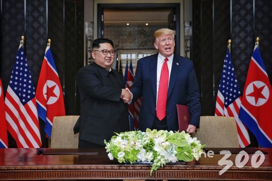 김정은 북한 국무위원장과 도널드 트럼프 미국 대통령이 12일 싱가포르 센토사 섬 카펠라 호텔에서 북미정상회담 공동합의문에 서명을 마친 뒤 악수를 나누고 있다. (싱가포르통신정보부 제공) 2018.6.12/뉴스1