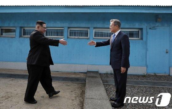 문재인 대통령(오른쪽)과 김정은 북한 국무위원장이 작년 4월27일 판문점 군사분계선 앞에서 만나 악수하기 위해 손을 내밀고 있다.. 2018.4.27/뉴스1 © News1 한국공동사진기자단