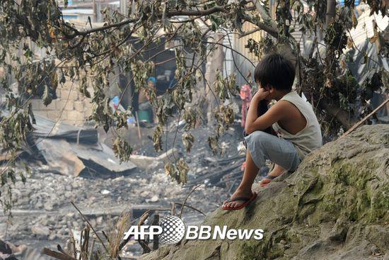 2015년 12월11일, 필리핀 마닐라에서 한 아이가 불에 탄 집을 바라보고 있다.