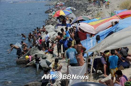 2015년4월4일, 필리핀 마닐라 슬럼가 거주민들이 마닐라 베이에 모여 더위를 달래고 있다. 당국은 '태풍 위험'이 있다며 수영을 금지했다. /AFPBBNews=뉴스1