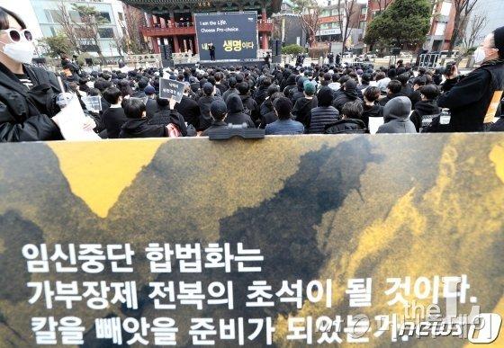 지난 9일 서울 종로 보신각 앞에서 열린 임신중단 전면 합법화 촉구 집회에서 한 참석자가 '낙태죄 위헌결정 촉구' 손피켓을 촬영하고 있다./사진=뉴스1