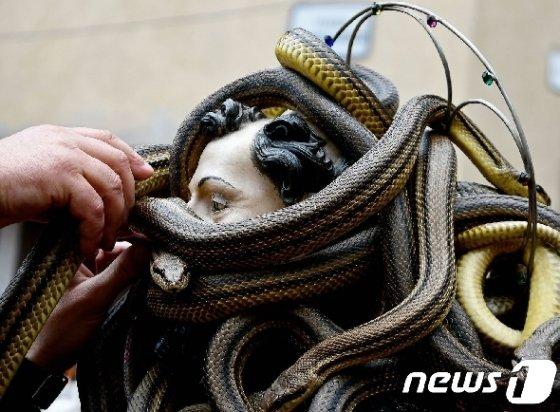 성상의 머리부분을 친친 감을 뱀들  © AFP=뉴스1
