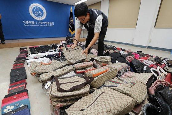지난해 7월 서울시 민생사법경찰단 관계자들이 명동에서 일본인 관광객들을 대상으로 판매되고 있는 짝퉁 명품 압수품을 공개하고 있다./ 사진=뉴스1