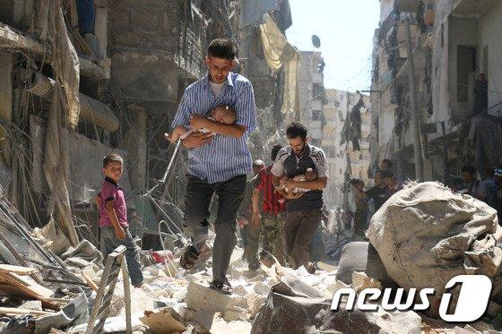2016년 9월 시리아 북부 알레포에서 한 남성이 아기를 품에 안고 공습으로 파괴된 건물 잔해 속을 걷고 있다./사진=AFPBBNews=뉴스1