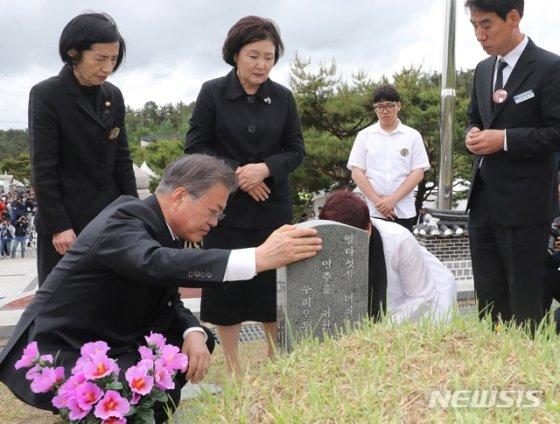 【광주=뉴시스】박진희 기자 = 문재인 대통령과 부인 김정숙 여사가 18일 오전 광주 북구 국립5·18민주묘지에서 열린 '제39주년 5·18민주화운동 기념식'을 마치고 5·18희생자 고 김완봉 묘역을 찾아 참배하고 있다.   고 김완봉(66년 7월 24일부터 80년 5월 21일)씨는 친구와 절을 간다며 길을 나셨다가 사망했고, 어머니는 적십자병원에서 아들 시체를 찾았고 29일까지 아들을 지키다가 묘역에 안장했다. 2019.05.18.    pak7130@newsis.com