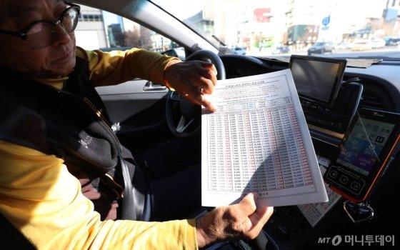 지난 2013년 10월 이후 5년 4개월만에 택시요금이 인상된지 이틀째인 지난 2월17일 오전 서울 시내의 한 택시기사가 요금 조견표를 설명하고 있다./사진=김휘선 기자 hwijpg@