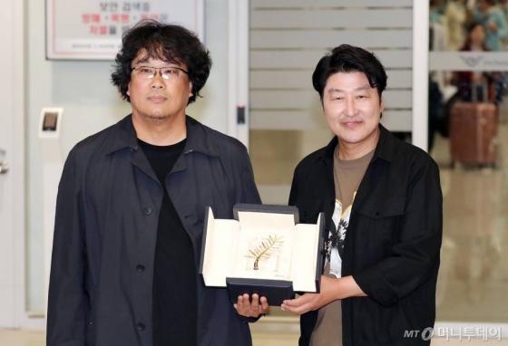 영화 '기생충'으로 한국 영화 최초로 황금종려상의 영예를 안은 봉준호 감독과 주연배우 송강호가 27일 오후 인천국제공항을 통해 귀국하며 상패를 들어보이고 있다. / 사진=김창현 기자 chmt@