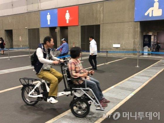참관객들이 도요타 티라이크의 자전거를 시험운행해보고 있다.