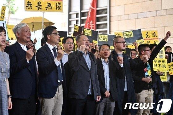 찬킨만 홍콩중문대 교수와 추이우밍 목사 등 9명의 2014년 홍콩 우산혁명 지도자들이 지난4월9일 홍콩의 법원에 출두하기 전에 구호를 외치고 있다. / AFP=뉴스1