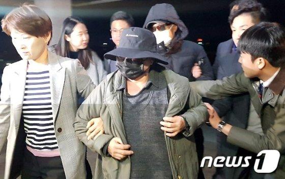 래퍼 마이크로닷(본명 신재호·26)의 부모가 지난 4월 충북 제천경찰서로 압송되고 있다./사진=뉴스1