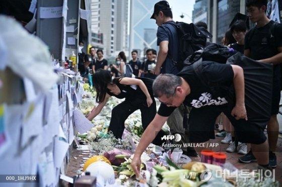 홍콩 시민들이 16일 '범죄인 인도 법안' 반대 시위에 참석하기 앞서 전날 오후 늦게 고공 시위 중 사망한 한 시민을 추모하기 위해 꽃을 놓고 있다. / 사진=AFP