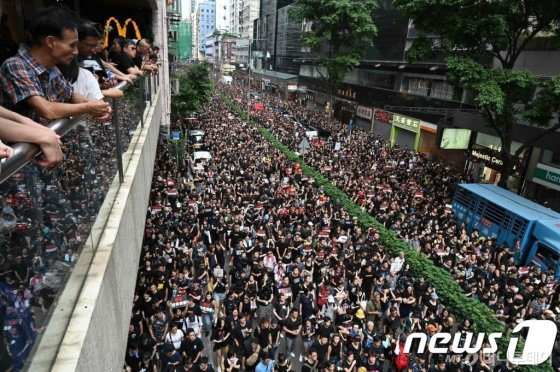 (홍콩 AFP=뉴스1) 우동명 기자 =  16일(현지시간) 범죄인 인도법 철회를 주장하는 홍콩 시민들이 검은색 옷을 입고 대규모 시위를 벌이고 있다. 이날 시위는 200만명이 참여해 이번 사태 이후 최대 규모로, 범죄인 인도법 완전 철회와 캐리 람 홍콩 행정장관의 퇴진을 요구하며 시내 곳곳에서 '검은 대행진'을 벌였다.   © AFP=뉴스1  <저작권자 © 뉴스1코리아, 무단전재 및 재배포 금지>
