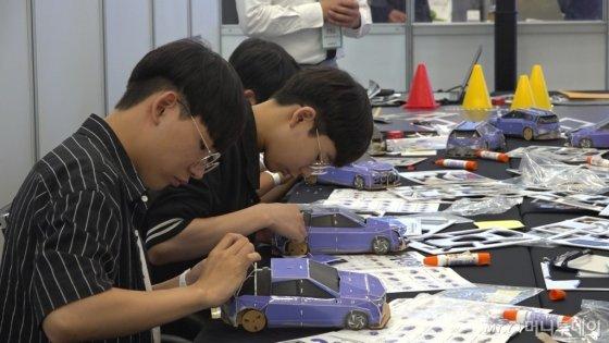 2019 수소엑스포 기간 중 현대모토스튜디오가 진행하는 자동차 체험 에듀테인먼트 프로그램 '키즈워크숍'에 학생들이 참가해 'DIY 넥쏘 자동차'를 만들고 있다. /사진=이상봉 기자