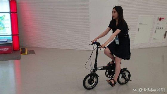 한국가스공사가 20일 서울 동대문디자인플라자(DDP)에서 열린 '2019 대한민국 수소엑스포'에서 중소기업 '한국에너지재료'가 개발한 고체 수소저장용기 활용 수소자전거를 선보였다. 기자가 직접 수소자전거를 타보고 있다./사진=김소영 기자