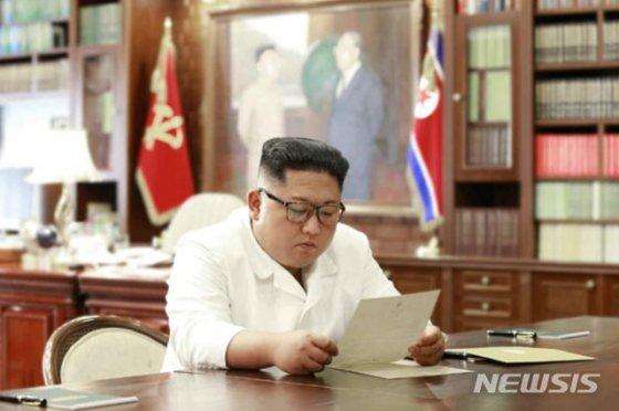 """【서울=뉴시스】 북한 노동신문이 23일 도널드 트럼프 미국대통령이 친서를 보내왔다며, 김정은 국무위원장이 친서를 읽는 모습의 사진과 함께 보도했다. 이날 김 위원장은 친서 받고, """"훌륭한 내용이 담겨있다""""며 만족을 표시하며, """"트럼프대통령의 정치적판단능력과 남다른 용기에 사의를 표한다고 하시면서 흥미로운 내용을 심중히 생각해볼것"""" 이고 밝혔다. 2019.06.23. (출처=노동신문)   photo@newsis.com"""