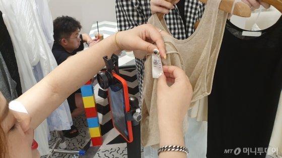 왕홍 양씨가 20일 동대문 한 쇼핑몰 매장에서 구독자에게 의류 소재가 설명돼 있는 라벨을 보여주고 있다. /사진=김태현 기자