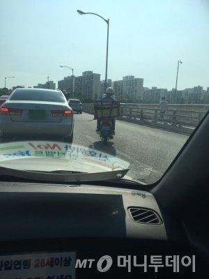 도로를 가르는 집배원 오토바이. 빨리 가려고, 어떻게든 간다./사진=남형도 기자