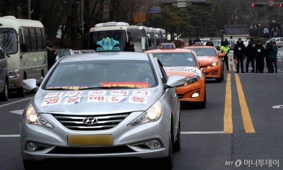 지난해 12월 카풀 도입 반대 문구를 택시에 부착한 채 대통령과의 면담을 요구한 뒤 떠나고 있다. / 사진=홍봉진 기자 honggga@