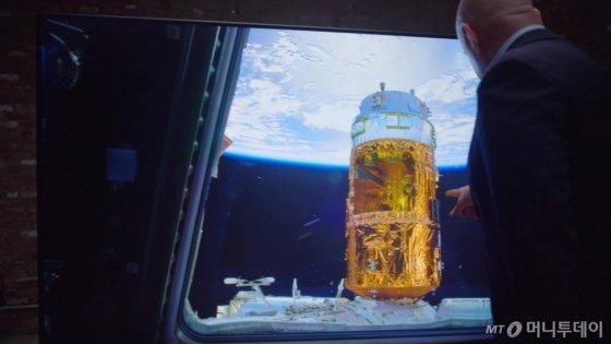 삼성전자가 달 착륙 50주년을 맞아 'QLED 8K로 본 우주'라는 콘셉트로 영상을 제작해 20일 공개했다. 사진은 이 영상 속의 한 장면으로 스콧 켈리가 우주에서 촬영한 지구의 모습을 삼성전자 QLED 8K TV로 감상하고 있다. /사진=삼성전자 제공<br />