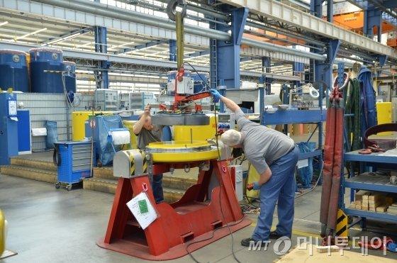 독일 노르트라인베스트팔렌주 뮐하임안더루르에 위치한 사용후핵연료 전용처분용기제작업체 GNS 공장에서 직원들이 완성된 처분용기 뚜껑을 점검하고 있다./사진=유영호기자 yhryu@