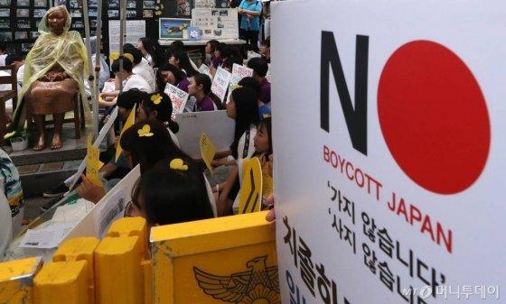 31일 오후 서울 종로구 옛 일본대사관 앞에서 '일본군 성노예제 문제 해결을 위한 정기 수요집회'에 참석한 학생들이 일본제품 불매운동과 관련한 피켓을 들고 있다./사진=김휘선 기자 hwijpg@
