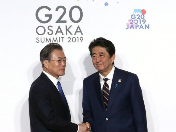 문재인 대통령이 지난달 28일 일본 오사카 국제컨벤션센터 인텍스오사카에서 열린 G20 정상회의 공식환영식에서 아베 신조 일본 총리와 악수하고 있다./사진=뉴시스