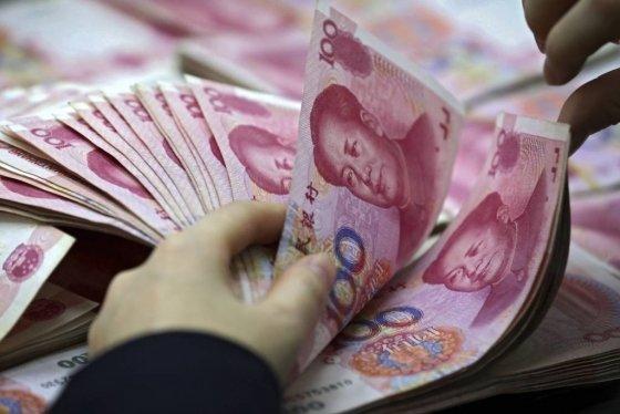 【화이베이=AP/뉴시스】중국 안후이성 화이베이시의 한 은행에서 직원이 위안화를 세고 있다. 17일 역외시장에서 위안화 가치가 폭락하며 위안화-달러 환율이 연고점을 기록했다. 2019.05.17.
