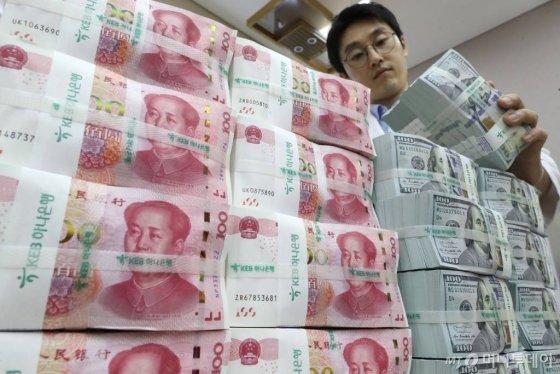 미국 재무부가 '1달러=7위안' 벽이 무너지면서 중국을 환율조작국으로 지정한 가운데 지난 6일 서울 중구 KEB 하나은행 위변조대응센터에서 직원이 달러화와 위안화 지폐를 점검하고 있다. /사진=이기범 기자 leekb@