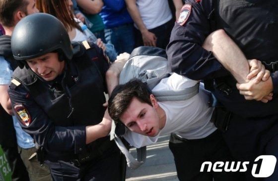 """5일(현지시간) 러시아 경찰들에게 체포되는 반정부 시위 참가자.외국 정부들과 인권 단체들이 1600명에 달하는 반(反)정부 시위대를 체포한 러시아 정부를 6일 강하게 비판했다. 유럽연합(EU)은 성명을 통해 러시아 경찰이 표현의 자유를 침해했다고 지적했다. EU는 """"일부 시위 참가자들이 (시위) 장소에 대한 승인을 받지 않았다 하더라도, 경찰의 잔혹함과 대규모 연행은 정당화할 수 없다""""고 밝혔다. 2018.05.06 /사진=뉴스1"""