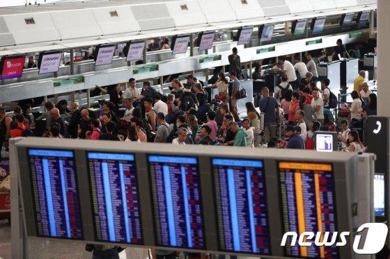 13일(현지시간) 운항이 중단됐던 홍콩 국제공항이 운항을 재개하자 탑승객들이 길게 줄을 서 있다. /사진=뉴스1