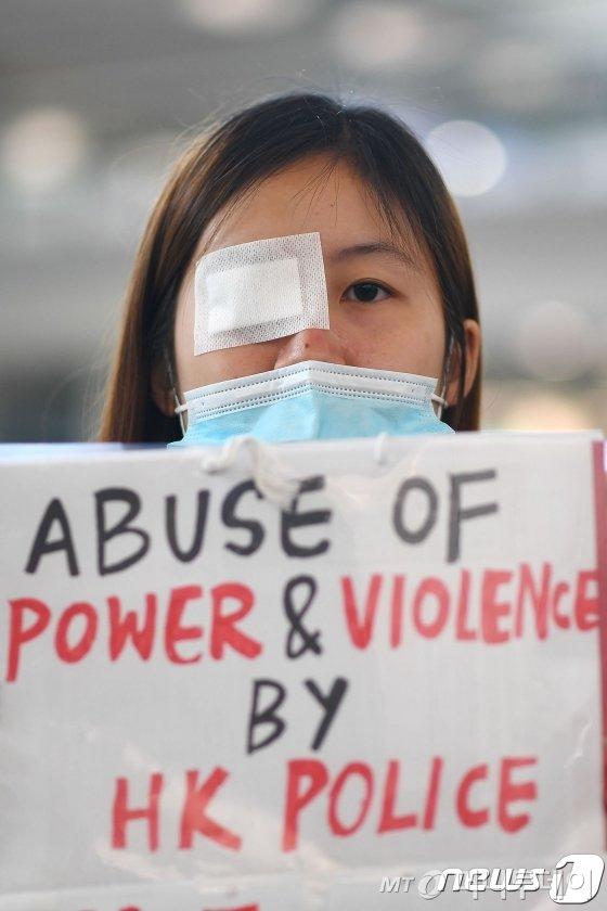 12일 (현지시간) '범죄인 인도 법안'에 반대하는 홍콩 시위대가 홍콩 국제공항에서 헝겊으로 한쪽 눈을 가린채 시위에 참여하고 있다. 시위대의 점거로 폐쇄됐던 공항의 운영은 13일 재개됐다./사진=뉴스1