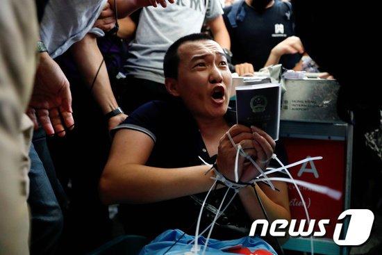 13일(현지시간) 중국 관영매체인 환구시보의 푸궈하오 기자가 시위대에 붙잡혀 있다. © 로이터=뉴스1