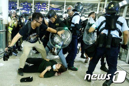 13일(현지시간) 홍콩의 시위 진압 경찰이 국제공항에 진입해 시위대와 충돌하고 있다. © 뉴스1