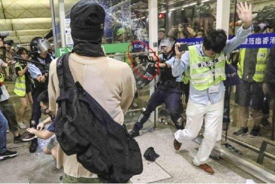 한 홍콩 경찰이 공항 시위 진압 도중 권총으로 시위대를 위협하고 있다 - SCMP 갈무리
