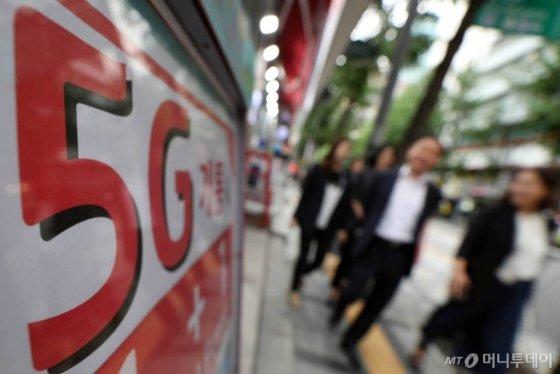5G 서비스 개통 100일이 되어가는 가운데 시민들이 10일 오후 서울 시내의 이동통신사 대리점앞을 지나고 있다./사진=임성균 기자