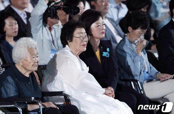 14일 서울 용산구 백범김구기념관에서 열린 2019년 일본군 '위안부' 피해자 기림의 날 기념행사에 위안부 피해자 이용수 할머니가 진선미 여성가족부 장관의 손을 꼭 잡은 채 공연을 보고 있다. 일본군 '위안부' 피해자 기림의 날은 1991년 8월 14일 일본군 '위안부' 피해자 고 김학순 할머니가 위안부 피해 사실을 처음으로 공개 증언한 날을 기념하고 김 할머니의 용기와 뜻을 이어받고자 지정됐다. 2019.8.14/뉴스1